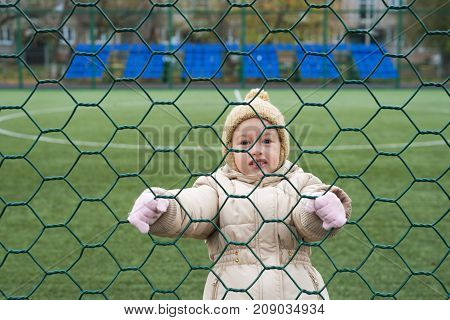 Little 4 year-old girl in a beige woolen hat and warm coat climbing a cell on a football field.