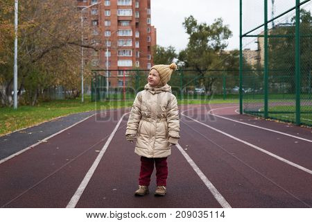 Little 4 year-old girl in a beige woolen hat and warm coat posing on a running track next to a football field.