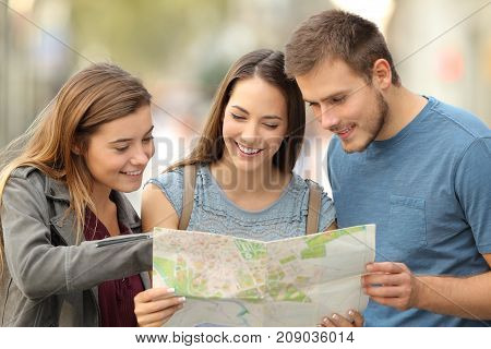 Three Tourists Consulting A Paper Map On The Street