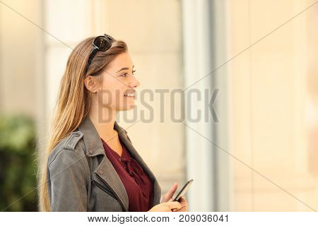 Happy Shopper Watching A Storefront Holding A Smart Phone