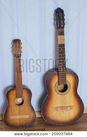 Two old broken guitars of a different size standing by the wall on the floor in the room: one is a regular one and another  is a child.