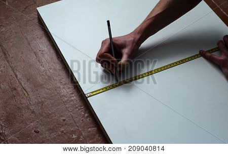 Carpenter Making Measurements On A Chipboard