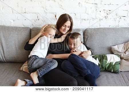 Portrait of happy young European female sitting on grey couch with two little sons who hugging her tight feeling need of her love and support. Two male siblings sharing attention of their mother