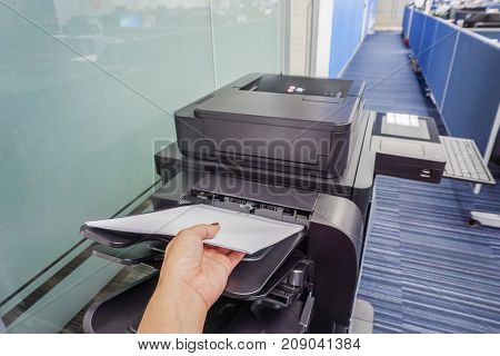 close up woman hand put paper sheet into office printer tray