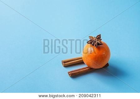 Tangerine on Cinnamon Sticks Imitating Sledges Anise Star Blue Background. Christmas New Year Greeting Card Poster Sales Template. Copy Space