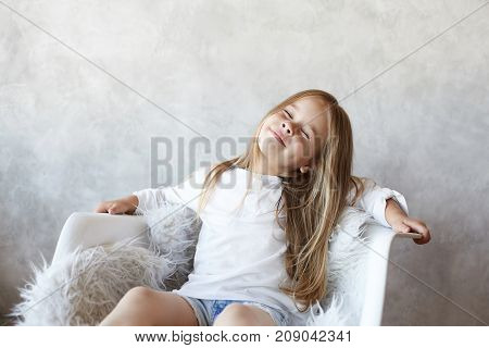 Indoor shot of playful cute little girl with fair hair wearing beautiful white blouse sitting in armchair and throwing her head back closing eyes fantasizing and dreaming about something pleasant