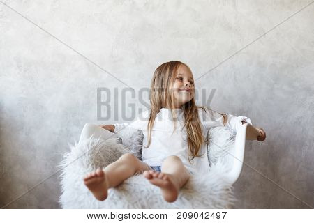 Happy childhood concept. Isolated shot of adorable European little girl relaxing barefooted on white comfortable chair and looking sideways with positive cute smile posing at blank grey wall