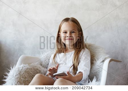 Beautiful female child with pretty smile typing sms to friend asking her out using free wifi on cell phonelooking at camera with positive joyful smile. Cute little girl enjoying online communication