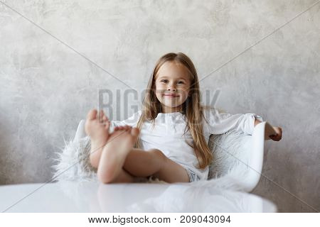 Cheerful pretty little girl with charming smile having relaxed and carefree look spending weekend morning at home sitting on white armchair resting bare feet on table ready to watch cartoons