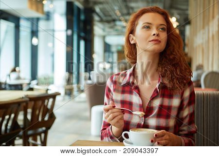 Happy young woman drinking coffee / tea  in a coffee shop