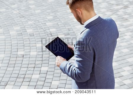 Businessman is holding tablet computer outdoors. Business concept