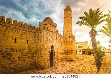 The walls and towers of the fortress of Ribat of Sousse in Tunisia. Medieval architecture in sunset light.