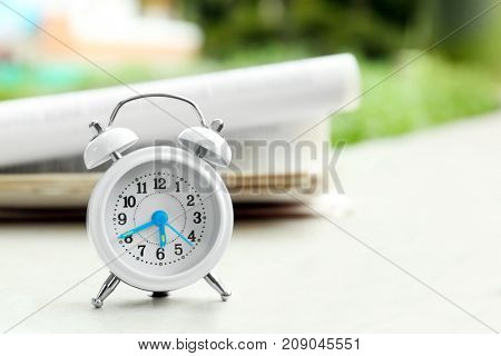 Alarm clock on parapet outdoors. Morning routine concept