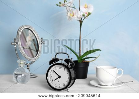 Composition with alarm clock on table in bedroom. Morning routine concept