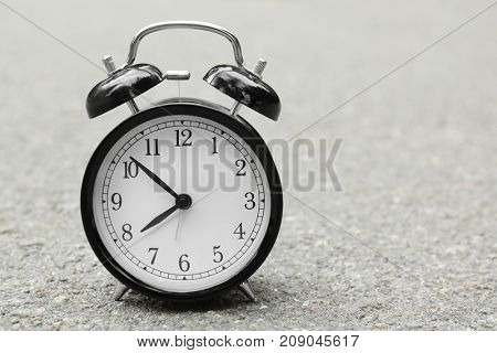 Alarm clock on asphalt outdoors. Morning routine concept