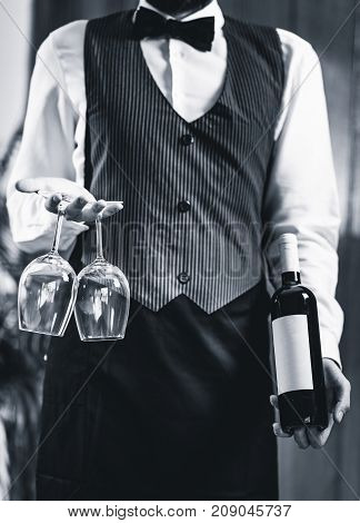 Sommelier Holding Wine Bottle And Wine Glasses, Black And White Image
