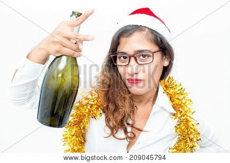 Close-up of confident young Asian businesswoman wearing Santa hat, glasses and tinsel holding champagne flute and showing victory sign. Christmas and office party concept