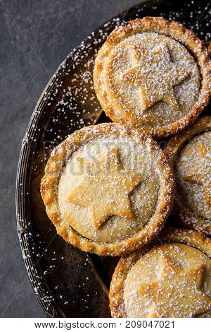 Traditional British Christmas Pastry Dessert Home Baked Mince Pies with Apple Raisins Nuts Filling Golden Shortcrust Powdered on Vintage Metal Plate Dark Concrete Background Top View