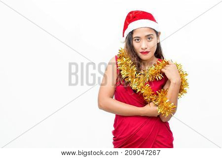 Portrait of happy young Asian woman wearing red dress and Santa hat and holding tinsel looking at camera. Christmas and New Year concept