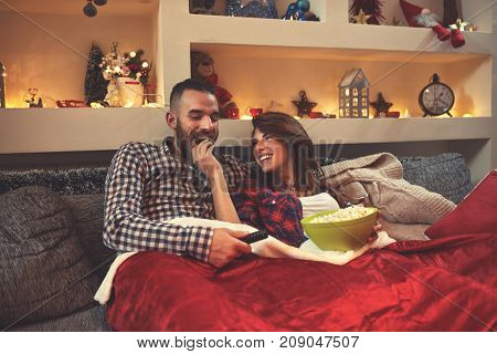 Young Chrismas couple enjoy together looking movie and eat popcorn in bed