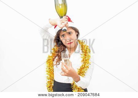 Portrait of sad young Asian businesswoman wearing Santa hat and tinsel holding flute and trying to pour wine from empty bottle. Christmas and alcoholism concept