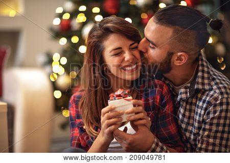 Young boyfriend kiss woman on Christmas Eve