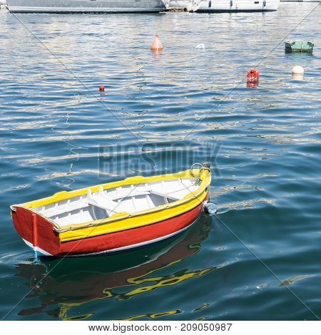 Colored buoys floating in port of Malta for mooring of yachts. A wooden cheap boat among the luxury ships