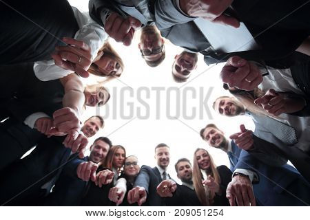 business team is forming a circle and pointing at the camera .