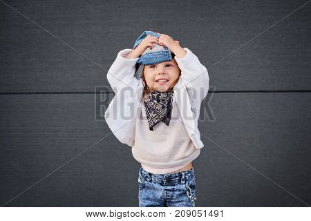 model child hip-hop.little baby girl in the baseball cap happy dancing in the background of the gray wall.Children's fashion.