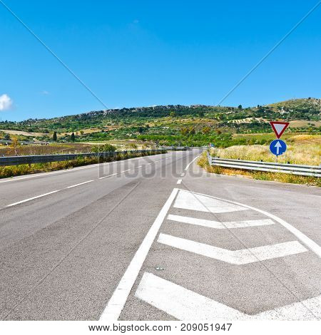 Winding Asphalt Road between Stubble Fields of Sicily. Highway Overpass in the valley in Sicily Italy.