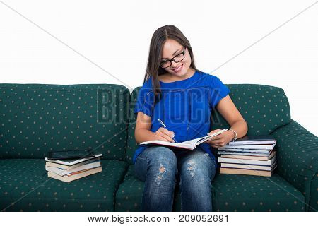 Student Girl Sitting On Couch Studying With Books Around