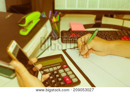 Businesspersons analyzing report business performance concept. Corporate businessman working at office desk he is using a calculator - Retro color