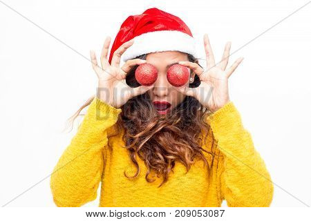 Amazed funny girl covering eyes with Christmas balls. Worried young woman with open mouth playing with Christmas ornaments. New Year coming soon concept