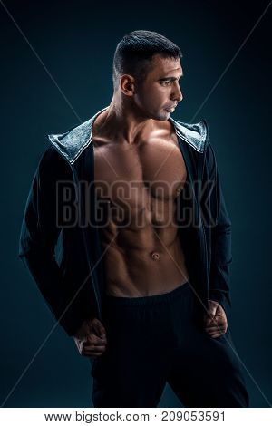Strong Athletic Man in Hoodie showing six pack abs.
