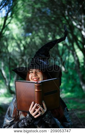 Image of smiling witch with magic book