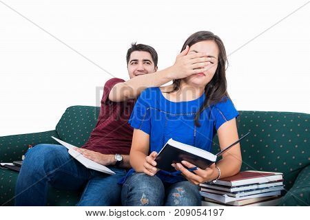 Student Couple Sitting On Couch Being Playful While Studying