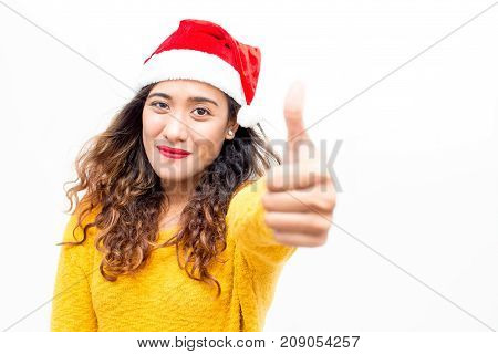 Cheerful beautiful young lady in Santa hat showing thumb-up as symbol of approval. Pleased content girl recommending goods. Time for discount concept