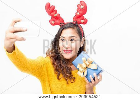 Cheerful pretty girl taking photo with gift for social media. Happy attractive young woman in reindeer antler headband making selfie. Christmas time concept