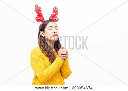Concentrated pretty woman asking God about gift of her dream. Pensive charming young woman with closed eyes praying before Christmas. Hope concept