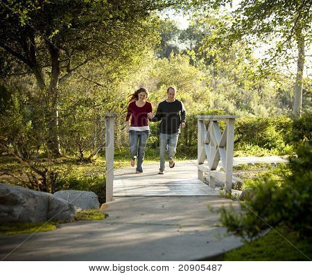 Couple Running on Bridge