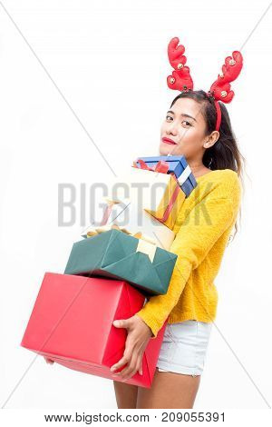Cool stylish girl in reindeer antler headband carrying stack of Christmas presents and looking at camera against white background. Smiling pretty woman buying gifts for friends. Christmas sale concept