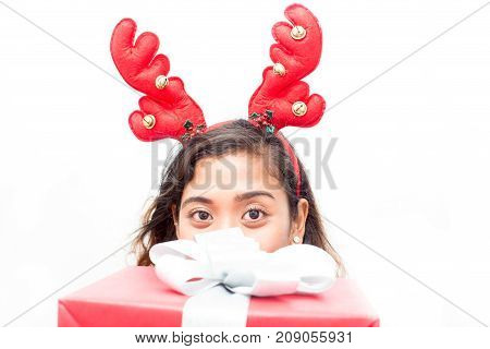 Funny young woman with antlers peeping over big gift box and looking at camera. Pretty girl in headband thinking of gift-giving. Christmas surprise concept