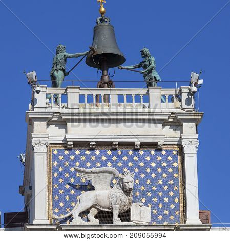 St Mark's Clock tower on Piazza San Marco Venice Italy. On the facade of the tower is the astronomical clock Lion of Saint Mark and Madonna with Child.At the top is a bell and Moors figures
