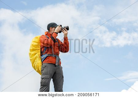 Picture of man photographer with camera and backpack