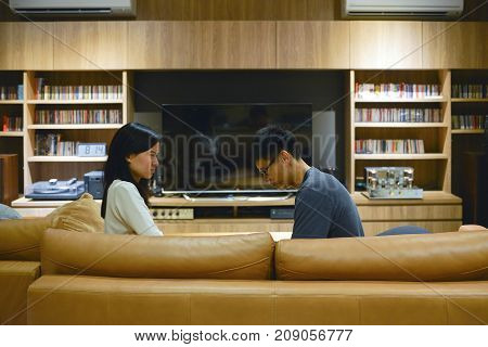 Angry Asian Wife Scolding Husband In Front Of Tv In Living Room At Night