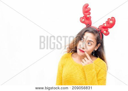 Pensive inquisitive woman in headband looking away and thinking of party. Serious concentrated girl touching corner of lips while choosing item. Decision concept