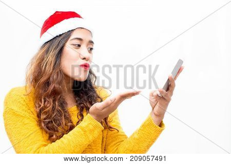 Pretty girl blowing kiss while making video call on phone. Happy attractive young woman talking to boyfriend via face time on smatphone. Technology concept