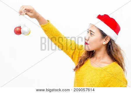 Pretty young woman holding Christmas balls and admiring decorations. Pensive girl in Santa hat preparing to decorate Christmas tree. Decorating home concept