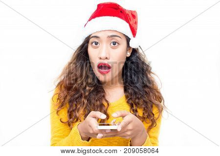 Shocked young woman with open mouth using smartphone and looking at camera. Astonished student girl in santa hat receiving message about Christmas sale. Spreading information concept
