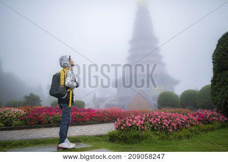 Young traveler boy with bag in beautiful fog garden.